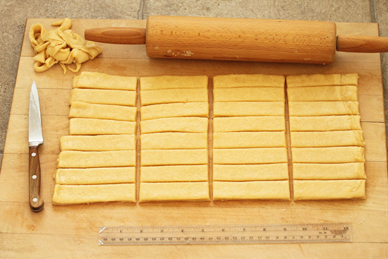 The cutting board is turned so the long side is facing you and the strips are cut in half, and each half divided in two to form 32 4x1-inch strips.